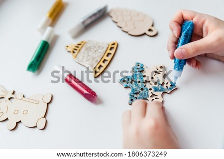 Christmas gifts. handmade Wooden toys.Making New Year decoration. Christmas ornaments. little child making Christmas decoration ornament .concept of creativity, handwork, preparation for the holiday. Royalty-Free Stock Photo #1806373249