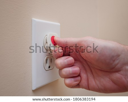 Electrical outlet with electricity safety cover to prevent child electrocution. Baby proofing household power sockets with plastic plug inserts. Royalty-Free Stock Photo #1806383194