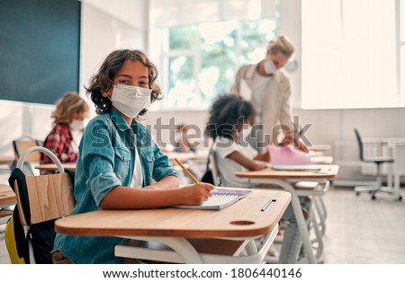 Multiracial pupils of primary school are ready to study after Covid-19 quarantine and lockdown. Children in class room with teacher wearing face masks and using antiseptic for coronavirus prevention. #1806440146