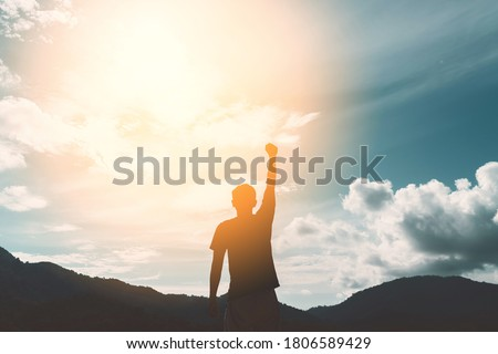 Copy space of man hand raising on top of mountain and sunset sky abstract background. Freedom travel adventure and business victory concept. Vintage tone filter effect color style. Royalty-Free Stock Photo #1806589429