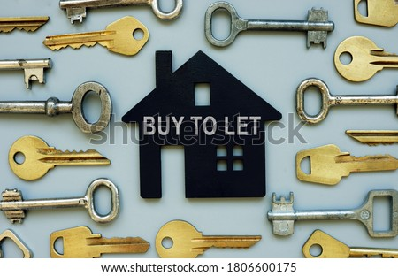 Buy to let concept. Lots of keys and a model of the house. Royalty-Free Stock Photo #1806600175