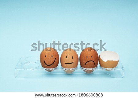 Chicken eggs in an egg holder. Full tray of eggs. Half an egg, egg yolk, shell. Emotion and facial expression painted on eggs #1806600808