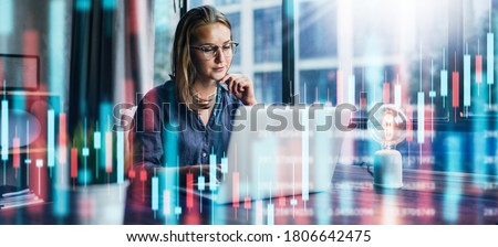 Young woman working at modern office.Technical price graph and indicator, red and green candlestick chart and stock trading computer screen background. Double exposure. Trader analyzing data Royalty-Free Stock Photo #1806642475