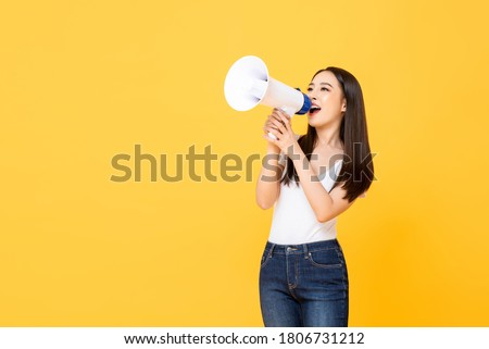 Portrait of smiling cheerful young pretty Asian woman holding megaphone making announcement in isolated studio yellow background