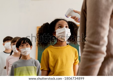 Group diverse students in school building checked and scanned for temperature check. Elementary pupils are wearing a face mask and line up before entering into classroom. Covid19 school reopen concept Royalty-Free Stock Photo #1806734899