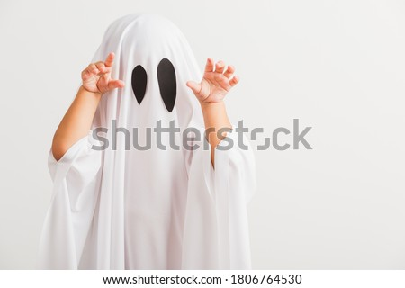 Funny Halloween Kid Concept, little cute child with white dressed costume halloween ghost scary, studio shot isolated on white background Royalty-Free Stock Photo #1806764530