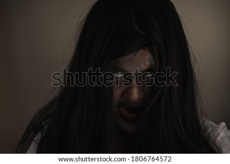 Woman zombie in blood. Closeup face and eyes of Asian Woman ghost with blood. Horror creepy scary fear in a dark house. Hair covering the face, Halloween festival concept #1806764572