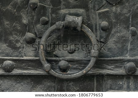 Detailed view of a very old and dark church door with rivets and a circular knocker handle #1806779653