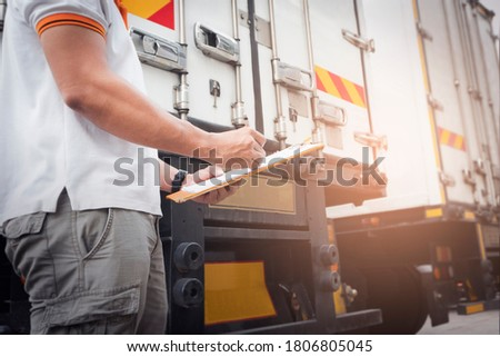 A truck driver holding clipboard his is checking safety of container truck steel door. Truck inspection and maintenance.   #1806805045