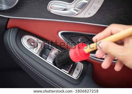 Auto detailer using detailing brush for cleaning dust in car window switch. Male hand cleaning car interior & upholstery with detail brush. Focus on brush. Car detailing concept. Car wash background. Royalty-Free Stock Photo #1806827218