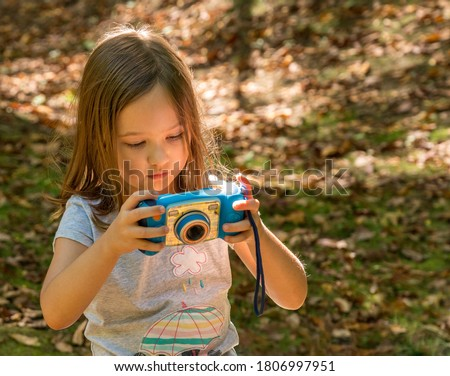 Small caucasian girl in a forest checking her photo on the back of a toy digital camera in concentration