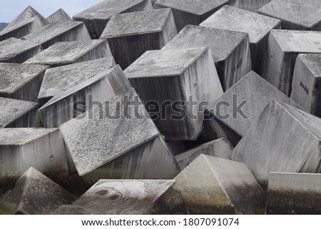 Concrete cubes used as breakwaters to protect the seaport. Royalty-Free Stock Photo #1807091074
