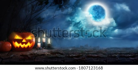 Jack O' Lanterns or Halloween pumpkins and candles glowing at moonlight in the spooky night. Halloween scene in a mystical forest with moon and scary sky .