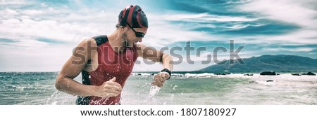 Triathlon competition swimmer man swimming looking at heart rate monitor tracker smartwatch. Panoramic banner. Outdoor sports. Royalty-Free Stock Photo #1807180927
