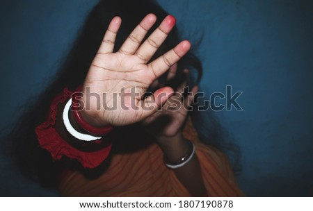 Indian housewife showing her hand for protecting herself from his husband.