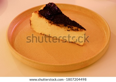 A picture with noise effect of burnt cheesecake serve in the cafe.