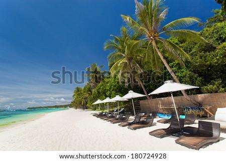 Sun umbrellas and beach chairs on tropical coast, Boracay  #180724928