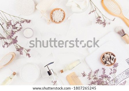 Soft cosmetic products and natural accessories for skin cleansing and body care with dry small flowers on light white background, flat lay, frame. Royalty-Free Stock Photo #1807265245