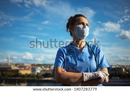 covid-19 pandemic. confident modern physician woman in scrubs with stethoscope, medical mask and rubber gloves looking into the distance outdoors in the city against sky. Royalty-Free Stock Photo #1807283779