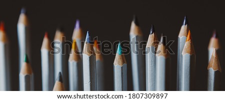 selective focus: many sharpened colored pencils that stand on a dark background with different heights and differ from each other