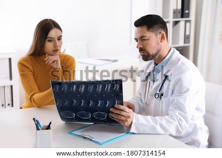 Orthopedist showing X-ray picture to patient at table in clinic
