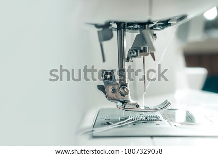 Mechanism of a sewing machine close up. White sewing machine needle with thread with copy space for text. The concept of the garment industry, technology. Photo for garment production. Royalty-Free Stock Photo #1807329058