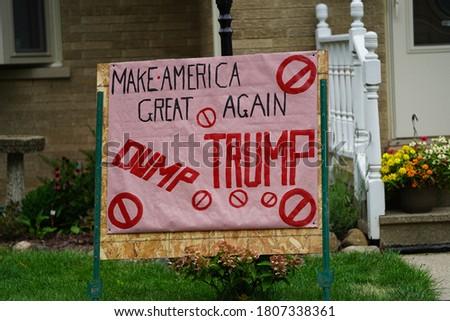 Anti-trump sign sits in a yard of a democrat