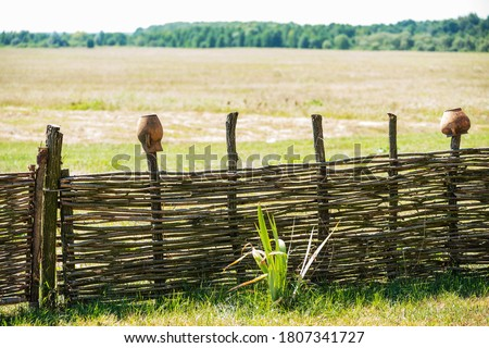 Fence wicker from the vine, texture, background. Wicker vine fence. woven vines texture embossed background. Organic woven willow wicker fence panel suitable for crafts, picnic or gardening background #1807341727