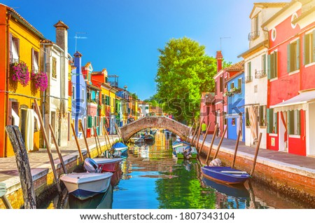 Colorful houses of Burano island. Multicolored buildings on fondamenta embankment of narrow water canal with fishing boats and stone bridge, Venice Province, Veneto Region, Italy. Burano postcard Royalty-Free Stock Photo #1807343104