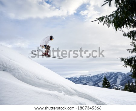 Side view snapshot of skier conducting extreme jump from a snowy slope, flying against amazing sky and mountain range on background. Copy space. Concept of skiing and winter sport activities. Royalty-Free Stock Photo #1807345366