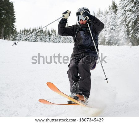 Man skier in black ski suit and goggles skiing downhill trough deep powder snow. Young man freerider in helmet using ski poles and gliding on snow at ski resort. Concept of skiing and active leisure. #1807345429