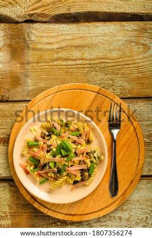 plate with pasta with ham and mushrooms in a creamy sauce on the table.