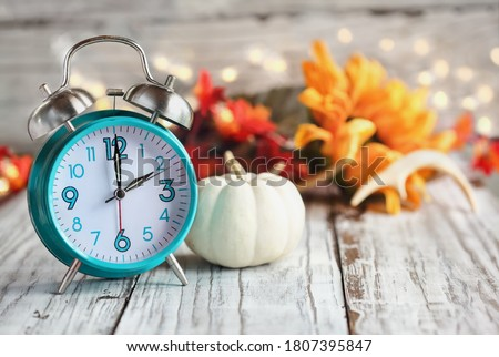 Set your clocks and fall back. Clock and decorations of mini pumpkins, colorful autumn leaves, antlers and bokeh lights over a white wooden table. Daylight saving time concept.