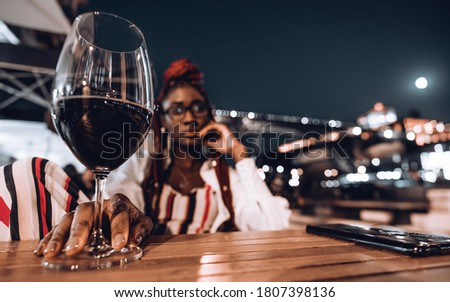 A night shot of a young black tourist woman in an outdoor restaurant with a shallow depth of field and selective focus on her hand on the table holding a glass of wine and a smartphone near; full moon