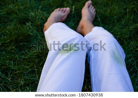 Girl's bare feet in the grass in the open.dirty grass stains on women's pants.daily life dirty stain for wash and clean concept Royalty-Free Stock Photo #1807430938