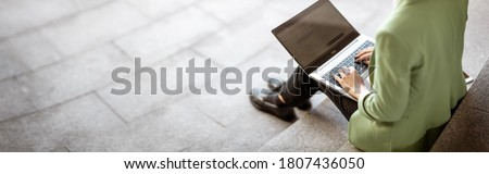 young woman with laptop sitting on the stairs. Person using personal computer outdoors Royalty-Free Stock Photo #1807436050