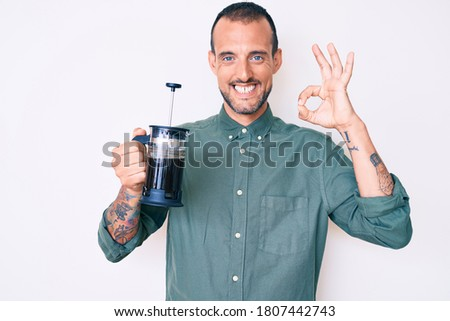 Young handsome man with tattoo holding french coffee maker doing ok sign with fingers, smiling friendly gesturing excellent symbol