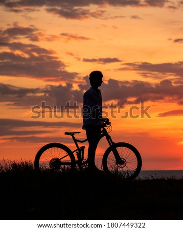 A young man with a Bicycle stands on a hill against the sunset sky. Black silhouette on a bright background. #1807449322