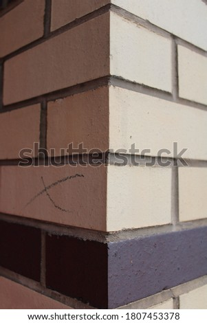 Close up corner of cream and black brick wall cemented bricks on exterior of bulding. For use in construction and building graphic and web design needs.  #1807453378