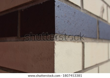 Close up corner of cream and black brick wall cemented bricks on exterior of bulding. For use in construction and building graphic and web design needs.  #1807453381