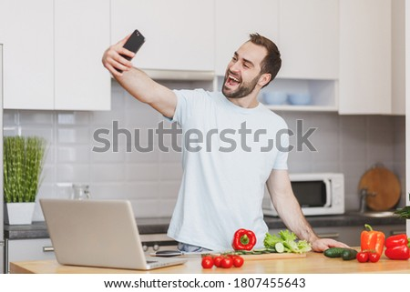 Excited fun happy young unshaven housewife man 20s in casual basic blue t-shirt doing selfie shot on mobile cell phone, preparing vegetable vegan salad, cooking food in light kitchen at home alone.