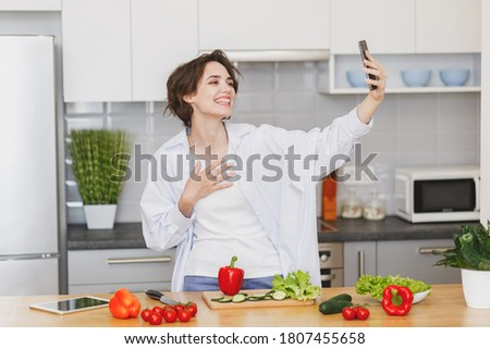 Cheerful young brunette housewife woman 20s in white husband's shirt basic t-shirt preparing vegetable salad cooking food in light kitchen at home, doing selfie shot on mobile cell phone video call.