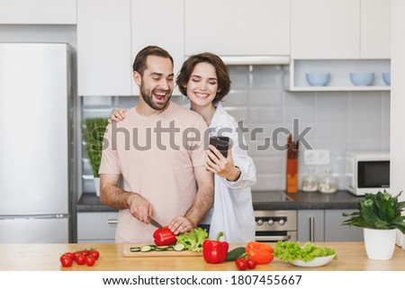 Fun smiling happy lovely young family couple woman and man in casual t-shirts clothes preparing vegetable vegan salad, cooking food in light kitchen at home together, doing selfie shot on mobile phone