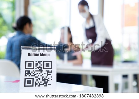 Asian waitress woman show qr code online menu for customer select meal in restaurant.New normal lifestyle sevice. Royalty-Free Stock Photo #1807482898