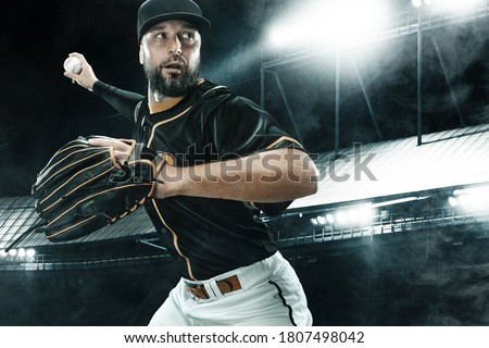 Porfessional baseball player with ball on grand arena. Ballplayer on stadium in action. Royalty-Free Stock Photo #1807498042