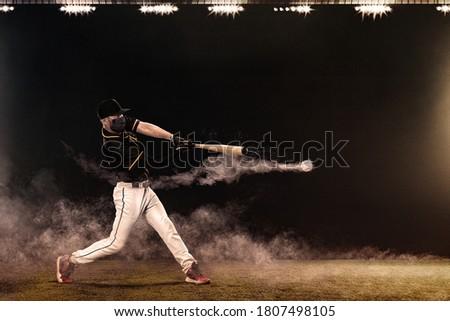 Porfessional baseball player in medical mask. Baseball game in 2020 - time of coronavirus pandemic. Ballplayer on stadium in action. Royalty-Free Stock Photo #1807498105