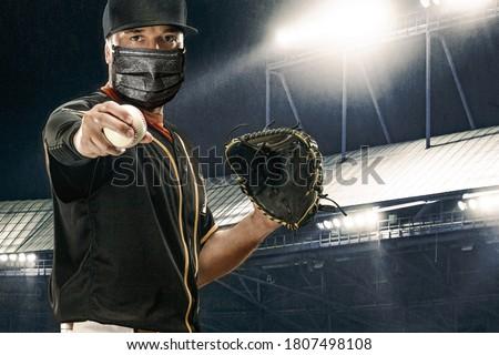 Porfessional baseball player in medical mask. Baseball game in 2020 - time of coronavirus pandemic. Ballplayer on stadium in action. Royalty-Free Stock Photo #1807498108