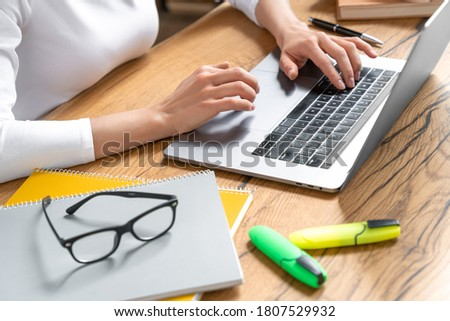 Close-up photo of female student hands using laptop app for work, studying, paying online courses at home after quarantine. E-learning concept with gadgets.