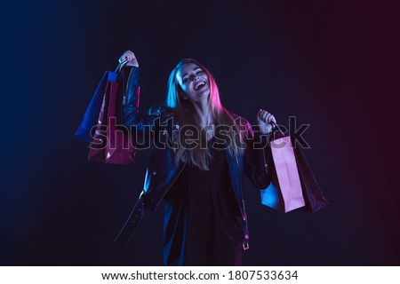 Portrait of young woman in neon light on dark backgound with shopping bags, black friday Royalty-Free Stock Photo #1807533634