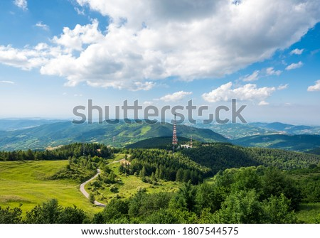 4G and 5G communication antennas at the top of the hill, near the inhabited centers. Wireless communication tower, in the background the blue sky. Royalty-Free Stock Photo #1807544575